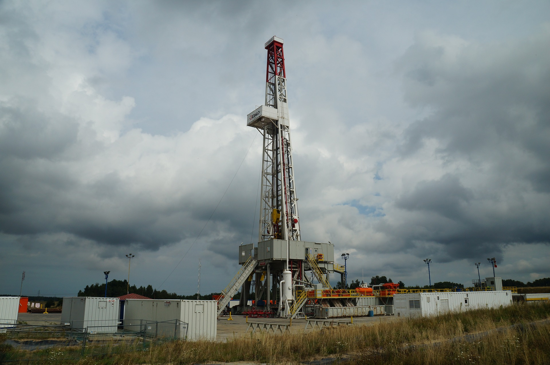 Image of a natural gas drilling rig set against a dark cloudy sky | TAB Bank