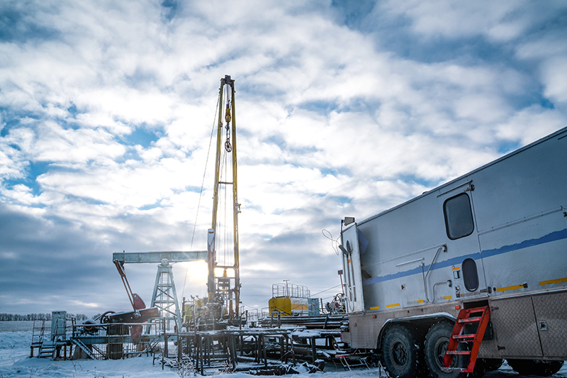 Image of wireline equipment hanging from top drive ready to be lowered downhole for logging. An oil well engineer works from the back of specialized van to log the condition of steel casing inside an oil well. | TAB Bank