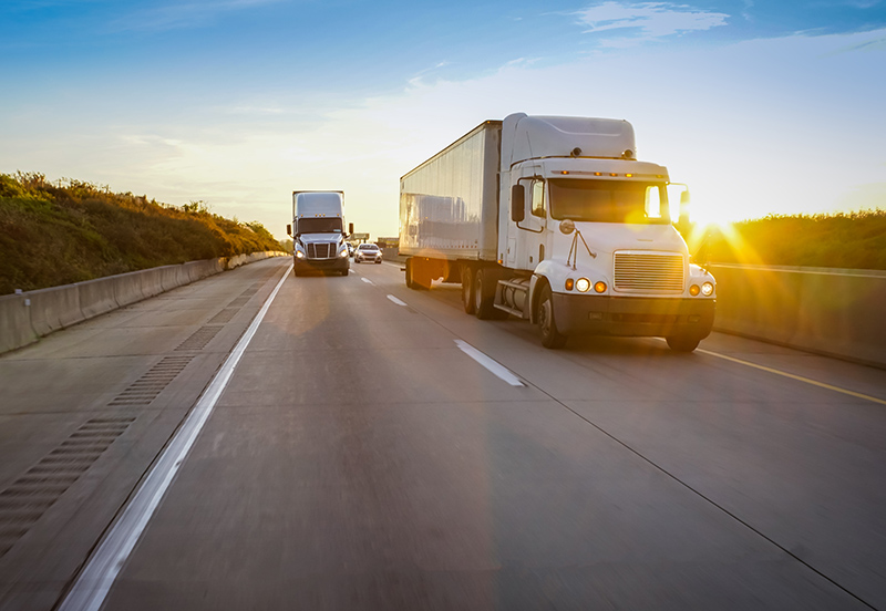 Image of two semi-trucks driving down freeway with the sun setting behind them | TAB Bank