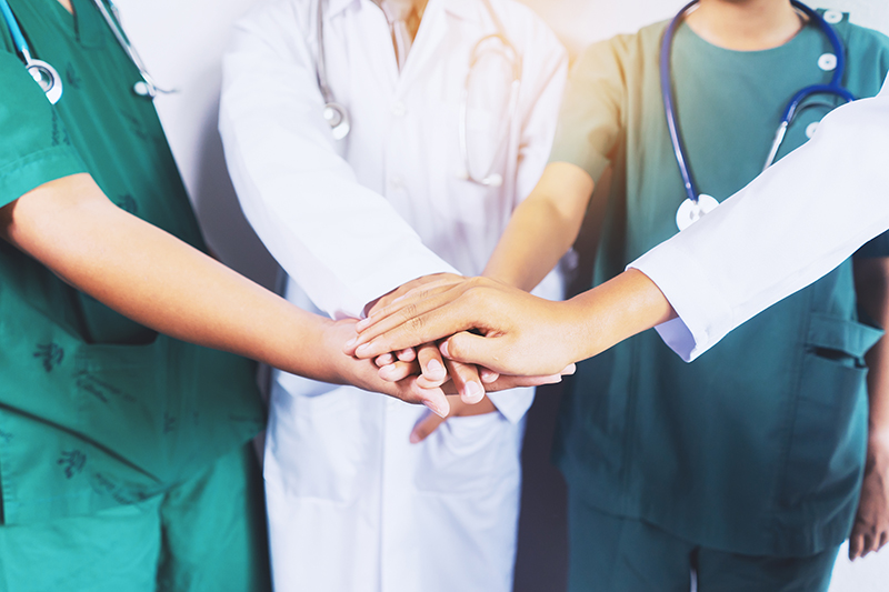 Image of medical personnel in a group with hands in the middle supporting each other | TAB Bank