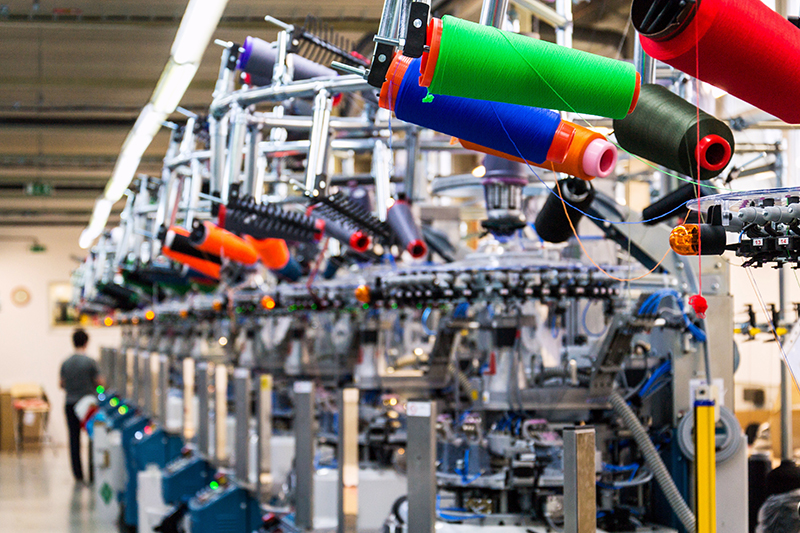 Image of textile factory and colors of thread on a industrial loom