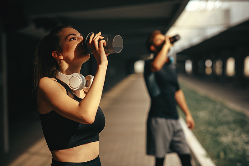 Image of a man and a woman in athletic clothes drinking from bottles during exercise