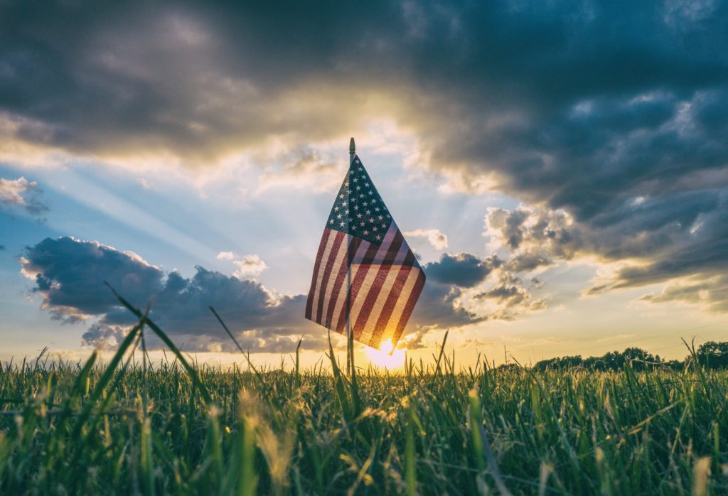 American flag waving over a field of corn in the setting sun