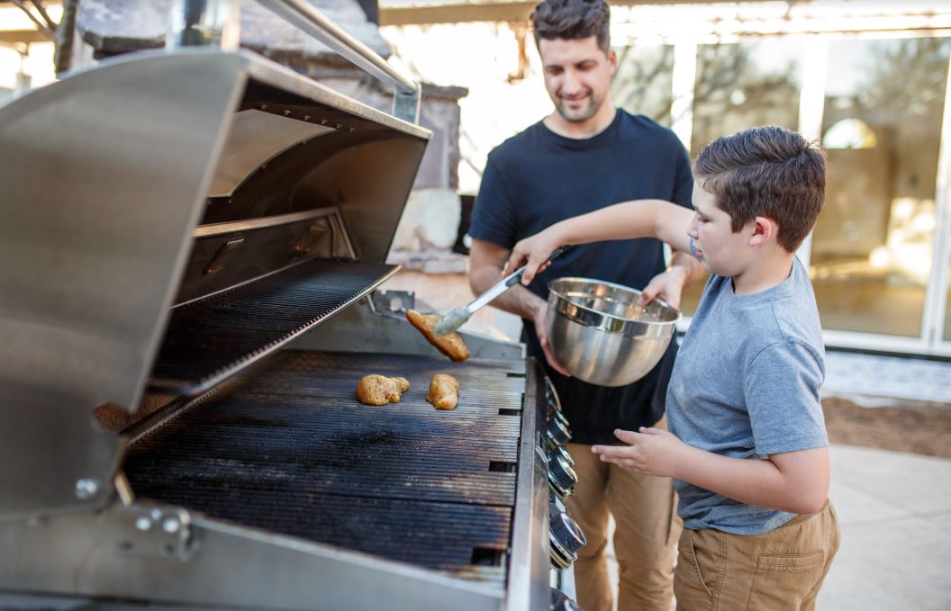 father and son grilling chicken