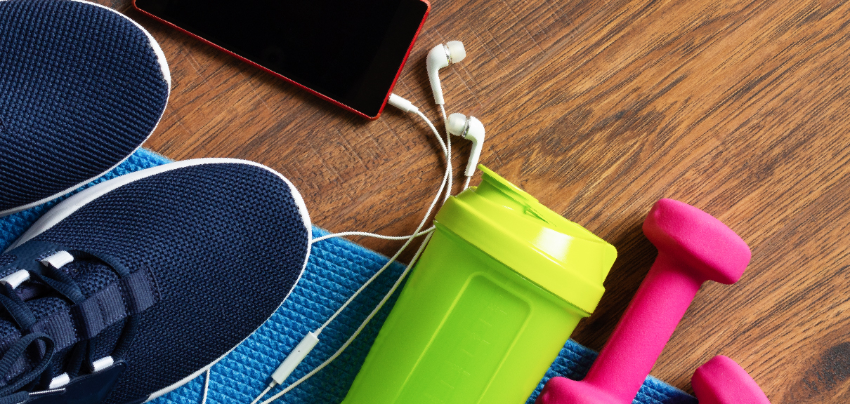 Wellness Ideas and Resources for Remote Workers - Fitness gear, shoes, headphones, water bottle, and phone on wood grain background
