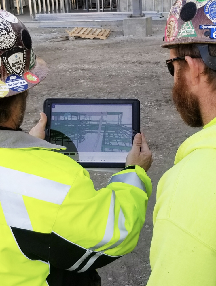 Two workmen onsite study tablet displaying 3D model in Trimble Connect