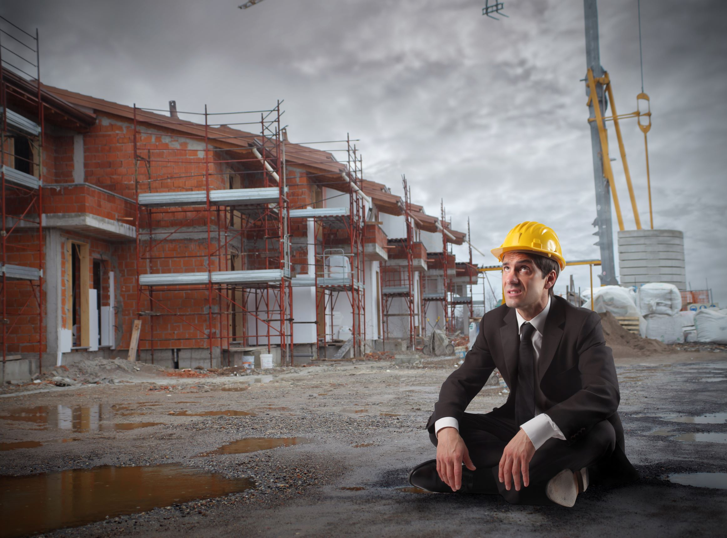 A man in suite sat on the floor in front of a building site.