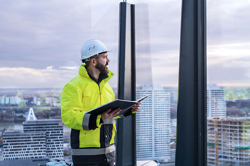 Builder checking plans at a highrise building