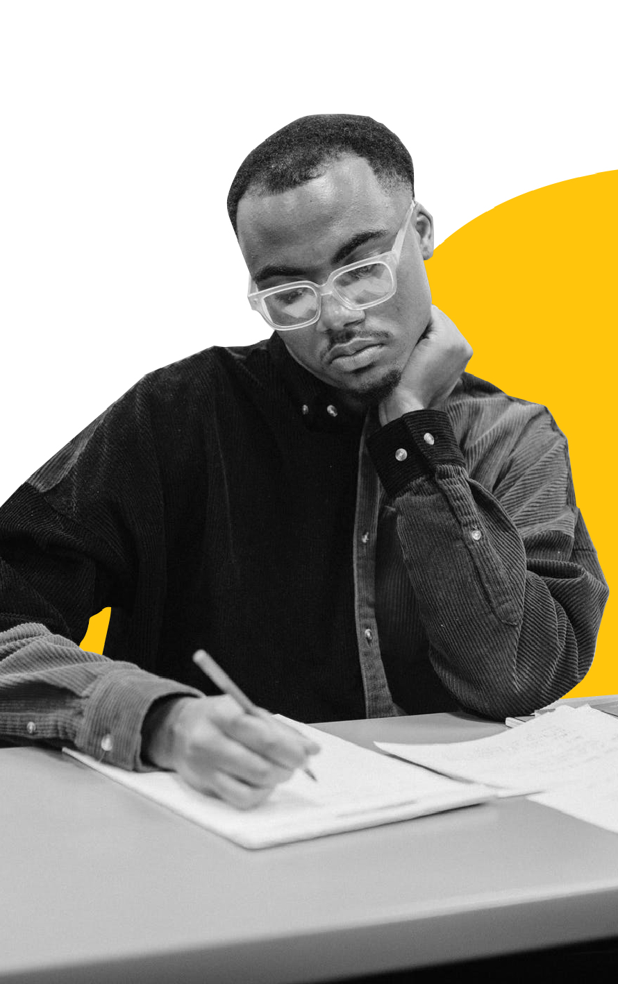 African man sitting at desk and writing in a notebook.