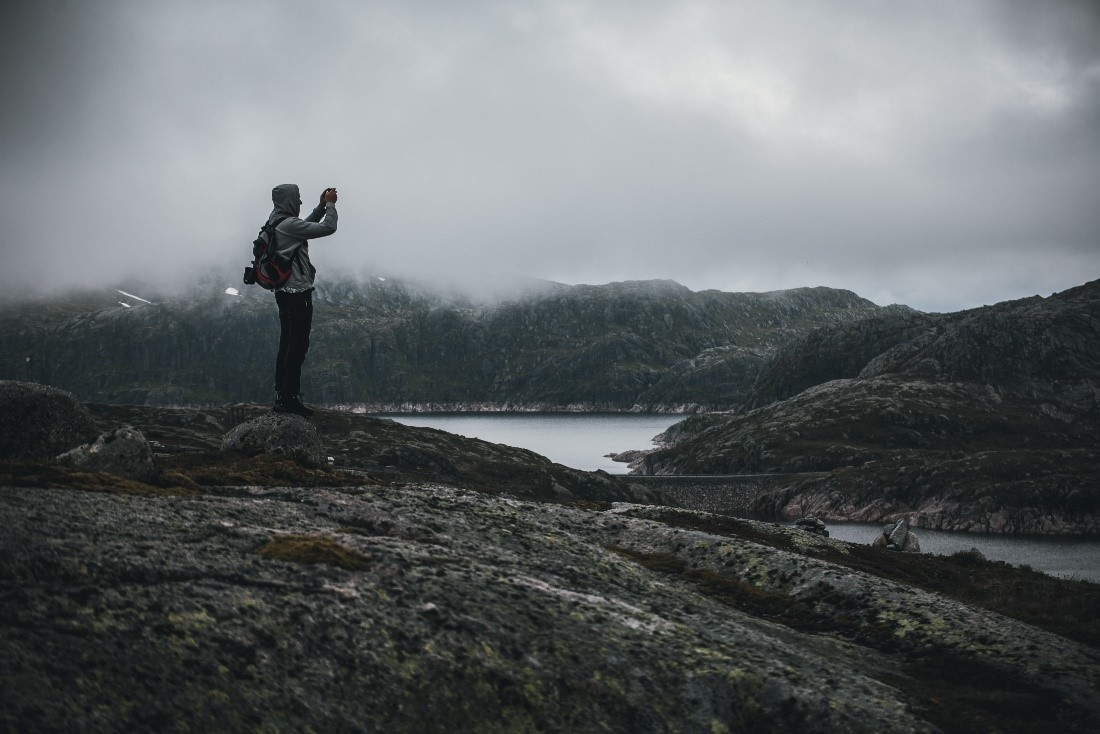Woman standing on rocky shore with fog