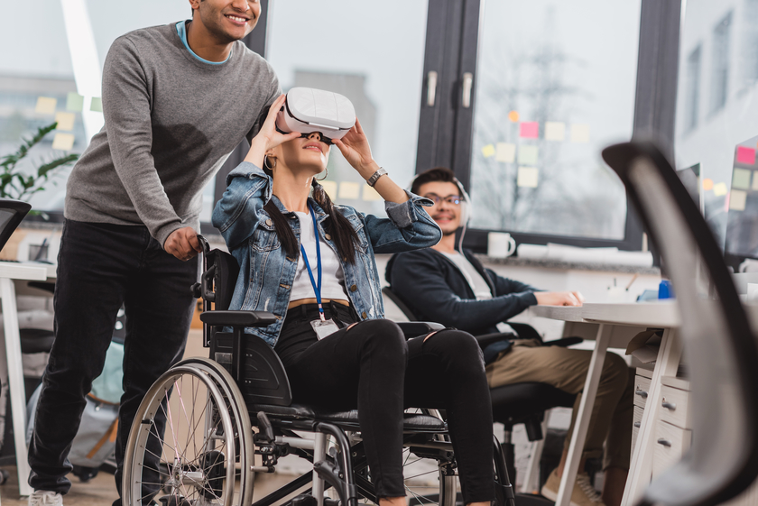 2 men watching a woman sitting on a wheelchair and using a VR headset