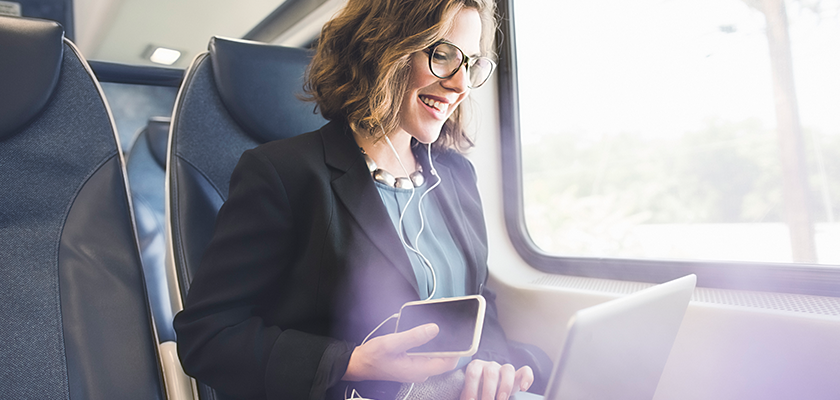 Woman sitting inside a train using a phone and laptop