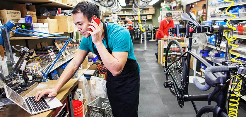 A man using his phone and laptop simultaneously who is in a bike repair shop wearing an apron