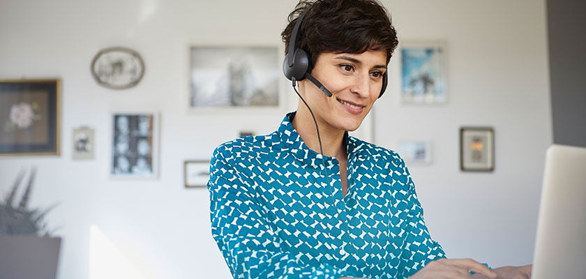 woman on headset working from home on laptop