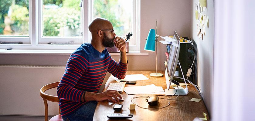 Man looking at laptop at desk at home