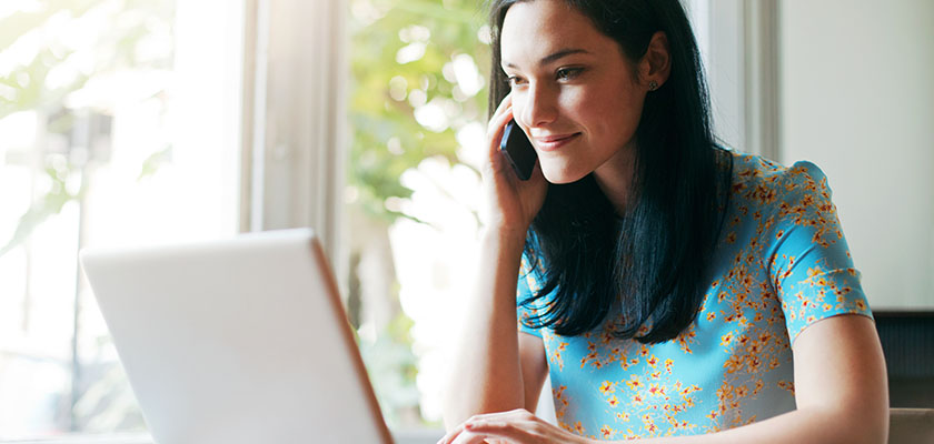 Woman looking at laptop at home desk