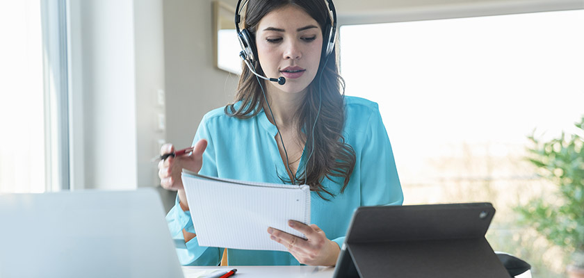 Woman wearing a headset reading notes