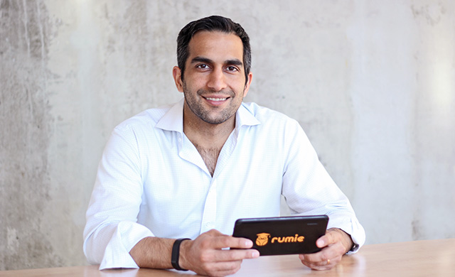 Man in a white shirt smiling and holding his phone