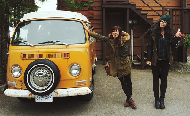 2 woman smiling and standing next to a yellow car