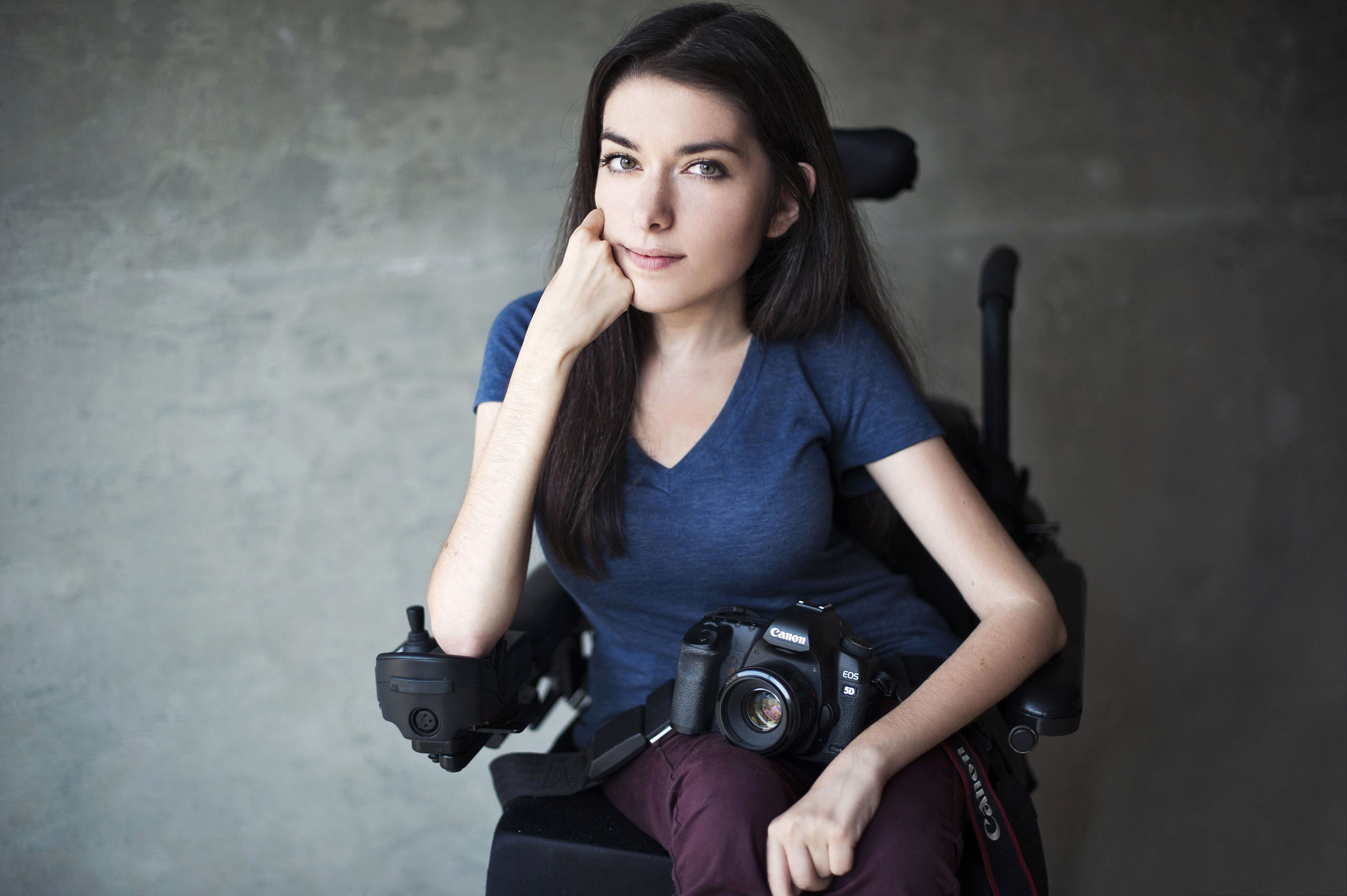 A woman sitting down with a DSLR camera on her lap