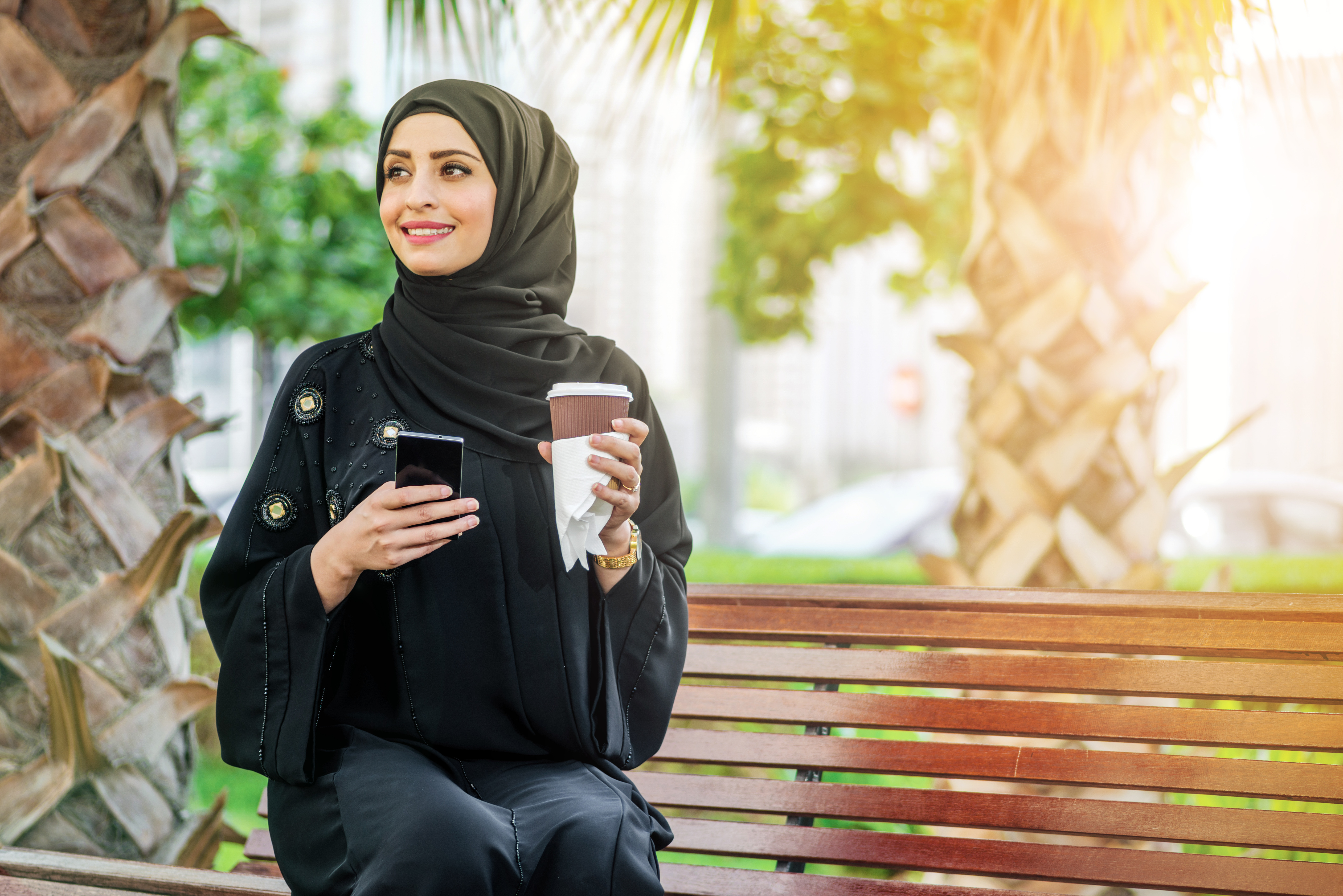 A woman sitting on a bench smiling holding a phone and coffee cup