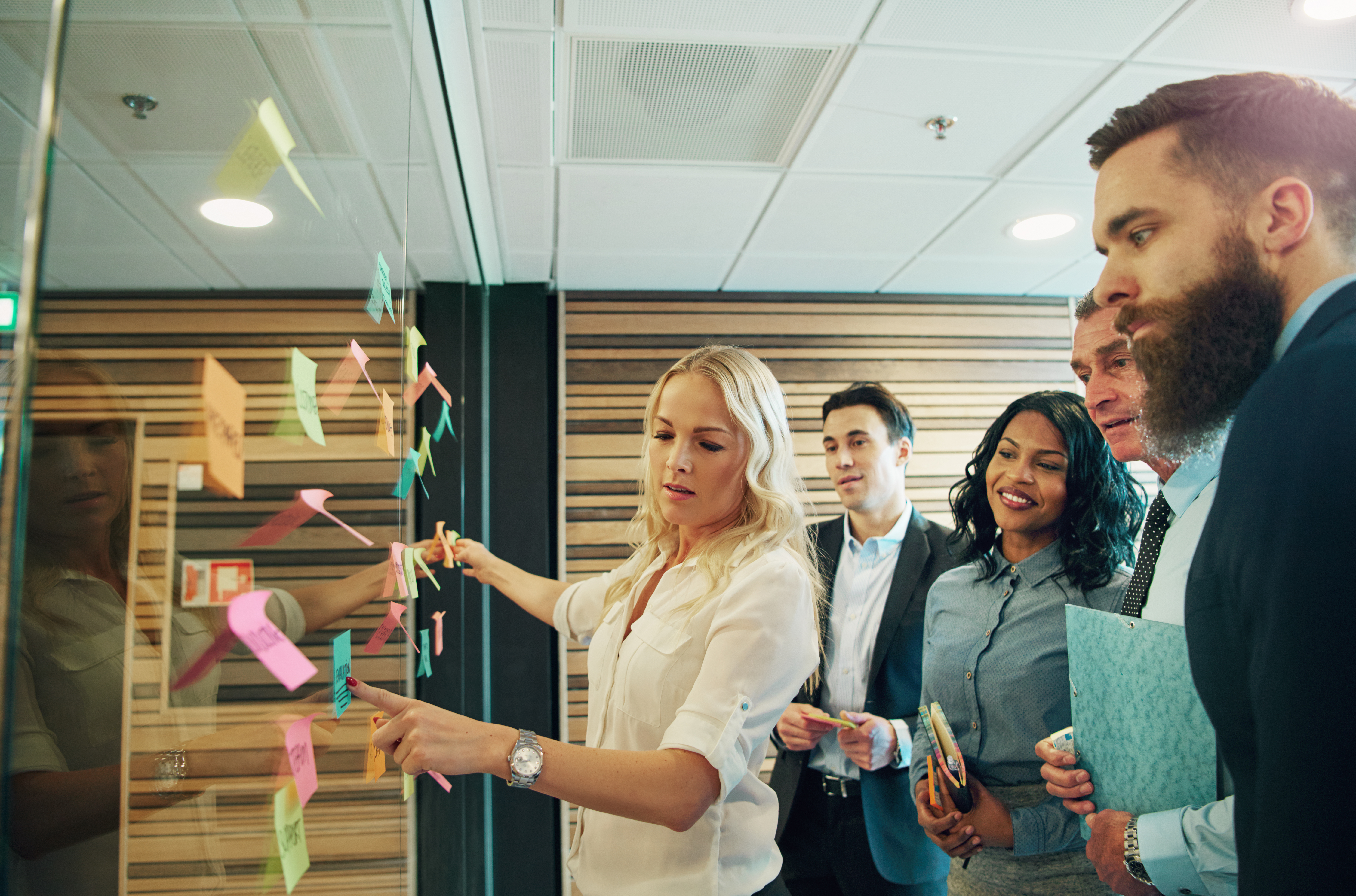 Group of people standing around a glass wall with stickies on it