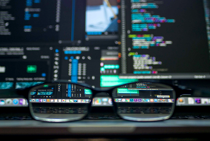 Computer monitor displays code, seen through the lens of eyeglasses sitting on a desk
