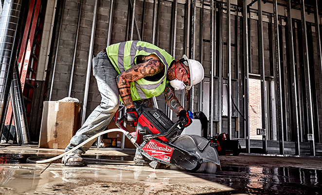 A tradesman uses the MX FUEL cut off saw to cut through concrete