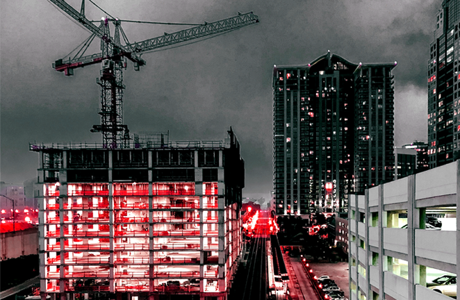 A construction site of a high rise is lit up at night in a city's downtown
