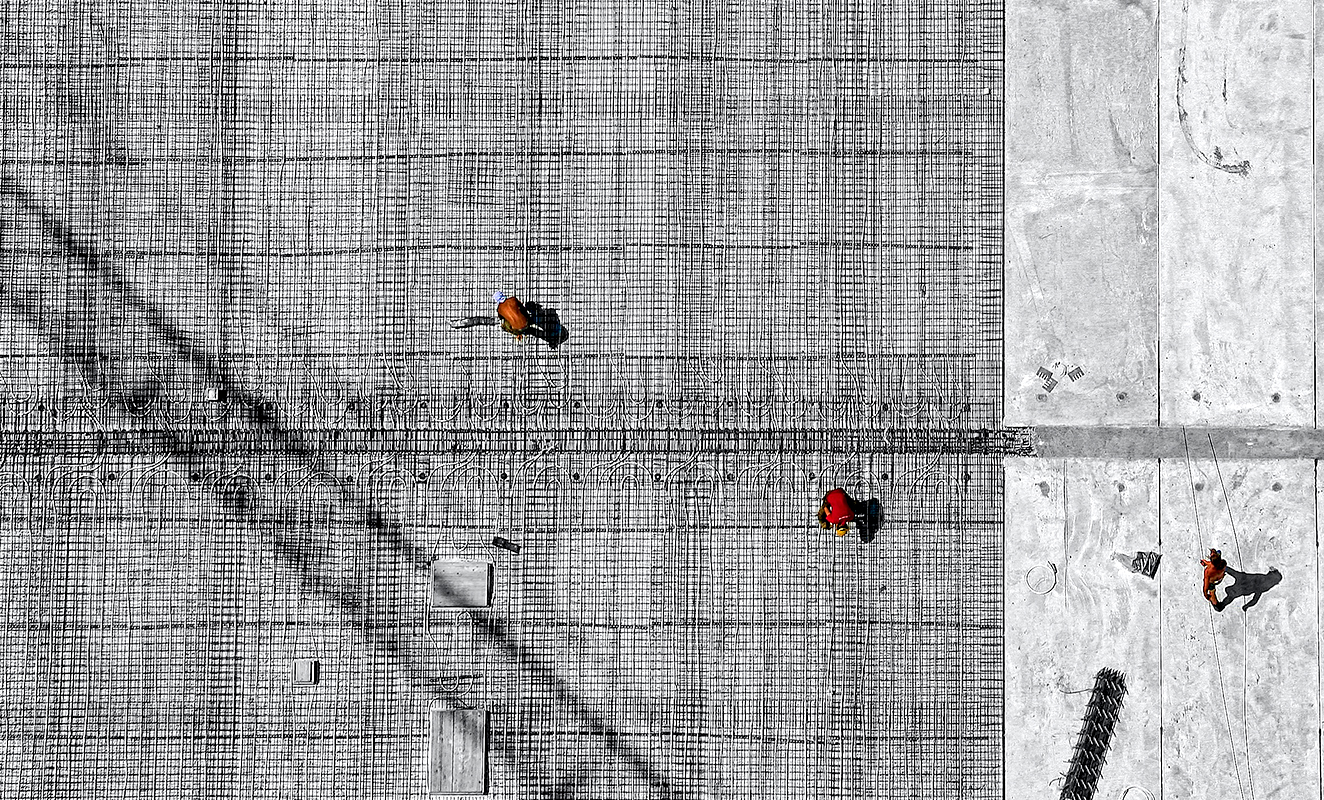 An aerial shot of construction workers on jobsite distanced from each other