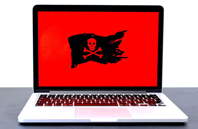 A laptop computer displays red background with black and red pirate flag symbolic of a cyber attack