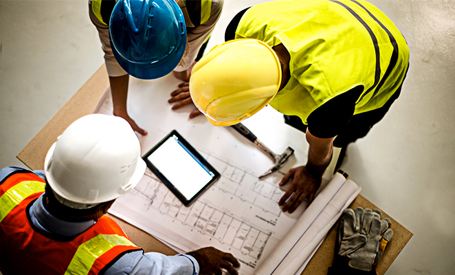 Construction workers wearing hard hats and high visibility vests huddle around building plans and tablet reader
