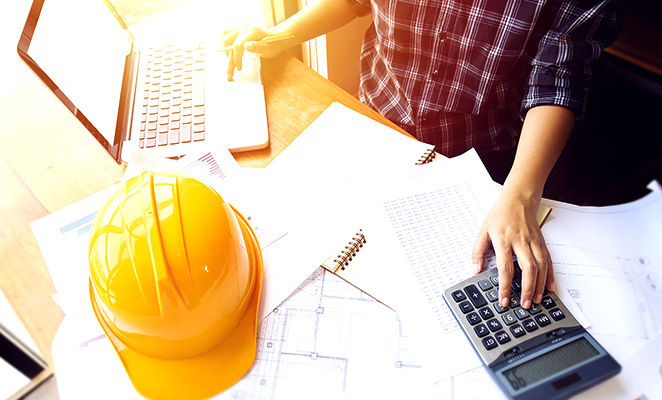 A construction manager at his laptop entering figures into calculator next to yellow hard hat