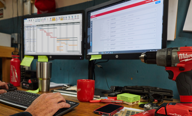 An inventory manager in tool room views spreadsheet and One-Key enterprise construction tool tracking inventory system