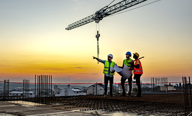 Three construction workers in high visibility vests and hard hats scan jobsite with one in the middle holding build plans