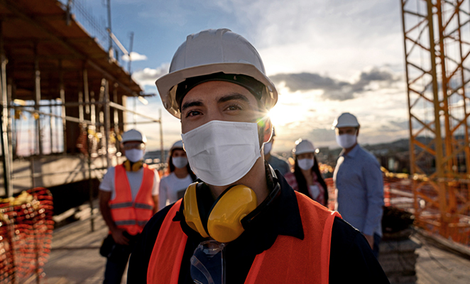 A masked contractor in a high-visibility vest leads a group of male and female workers on site