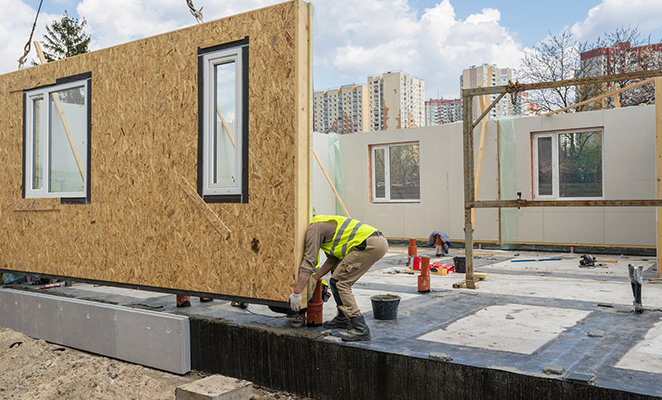 Construction worker installs prefabricated wall