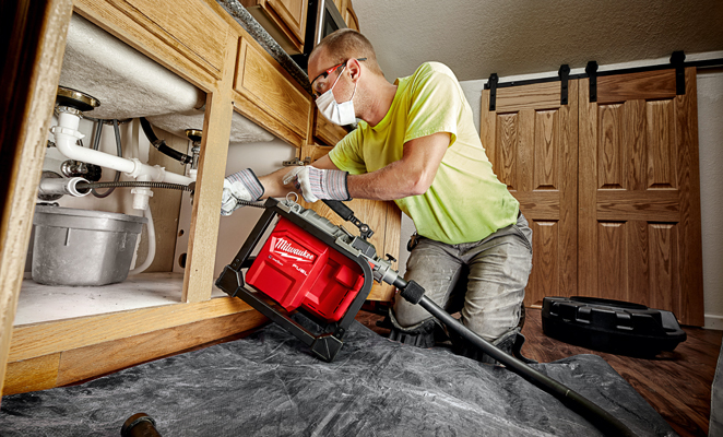 A plumber clears a kitchen sink drain utilizing a Milwaukee sectional drain cleaner