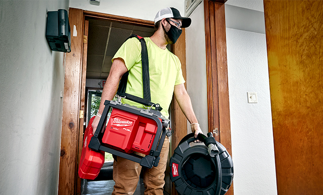 Plumber transports sectional plumbing equipment and drum machine into house