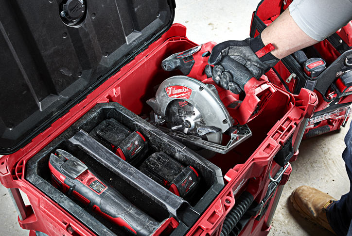 A contractor pulls a Milwaukee circular saw out of a PACKOUT stack