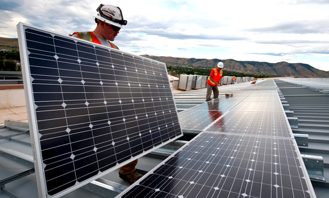 Two solar panel installers working in foreground, and one in background
