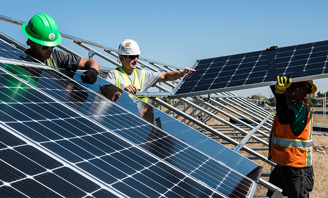 Three solar panel installers working, one of which oversees process