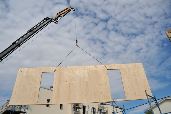 A prefabricated wall is craned into place