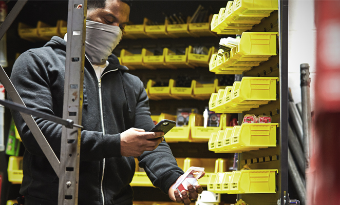 A tool room attendant scans bardcode with smartphone