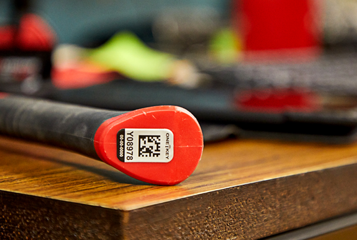 A One-Key asset ID tag is affixed to the bottom of a hammer