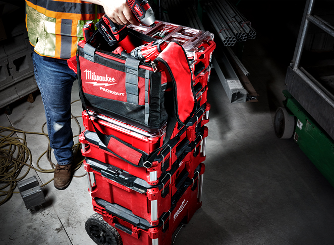 A construction tradesman holds a Milwaukee drill above a PACKOUT tool kit stack