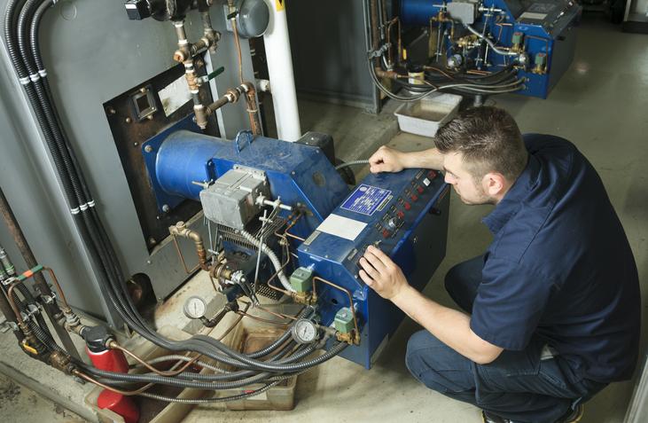 An industrial electrician repairing fixture