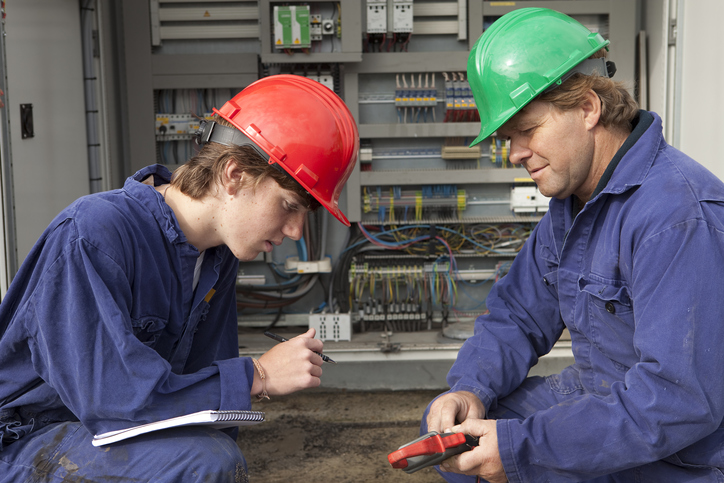 An apprentice learns from a master electrician