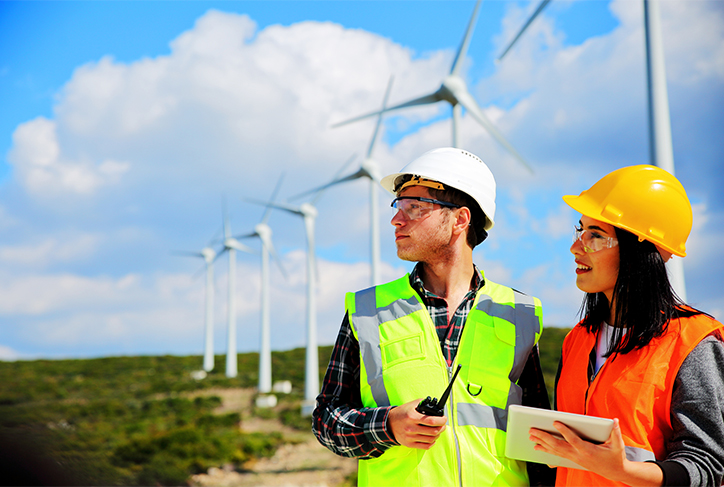 Two wind turbine technicians look into the distance
