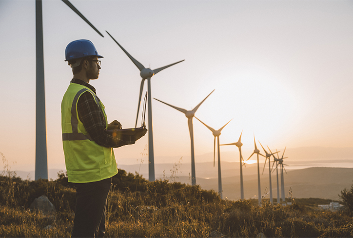 A wind turbine technician holds clipboard observing field nearing sunset